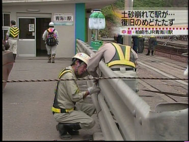 これから現場に通すためにガドレールを外しているところだった。確かに、ガードレールは邪魔だ(この重機ならガードレールを踏み潰して通れないことはなさそうだが)。(NTVの画面キャプチャ)